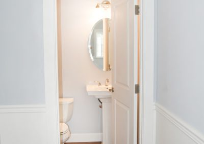 View of the first floor bathroom off the entrance hallway adjacent to the primary staircase.