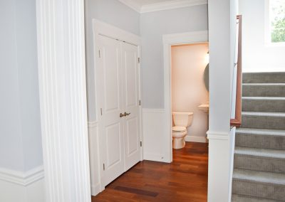 View of the coat closet, main floor bathroom, and staircase leading to the second floor.