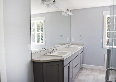 View into the master bedroom's en suite bathroom. Note the twin sink and 8-foot wide mirror.