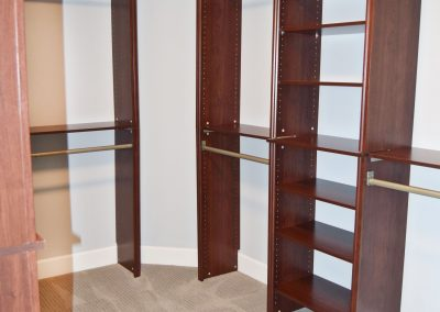 View of the master bedroom's walk-in closet with built in shelving.