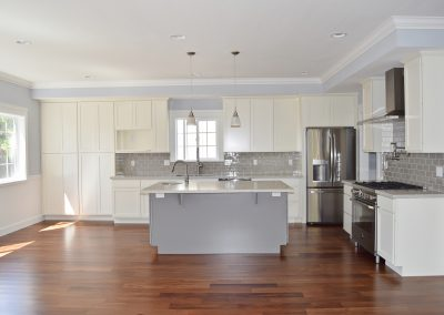 "View of a 500 square foot kitchen and living area. Note the crown moulding, island sink, and ample, ""family-of-five"" shelving. To the left of the island is a well-lit breakfast nook area."