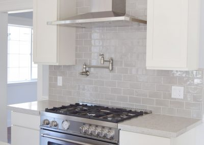 "View of the perfectly fitted, 5-burner gas-powered stove. Note that the ""Pot Filler"", the retractable faucet, perfectly complements the look and feel of the stove."