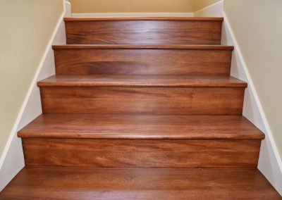 View of wide Craftsman style staircase with optional hardwoods.