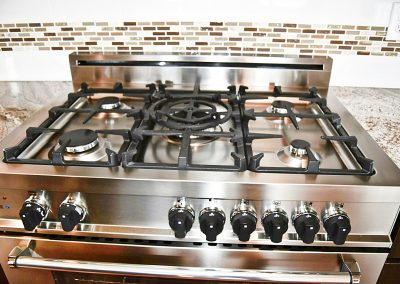 View of a five burner, gas-powered, stainless steel range.