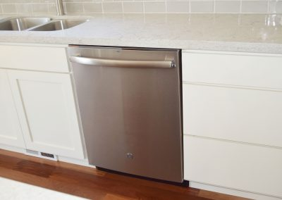 View of under counter stainless steel GE dishwasher.