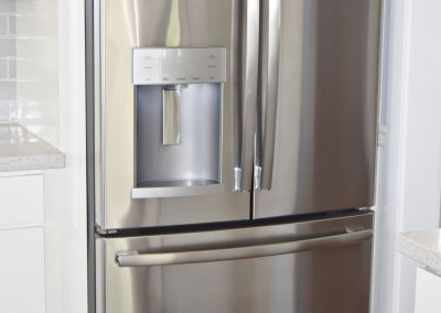 View of perfectly fitted stainless steel refrigerator with bottom freezer, built-in filtered water and ice dispenser.