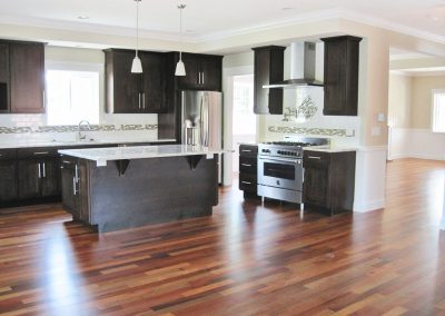 View of kitchen in open floor plan adjoining dining and living areas.