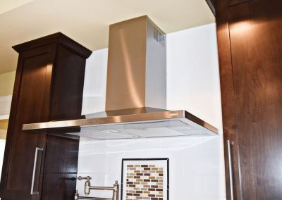 View of dual-fan stainless steel hood whose transitional design complements Craftsman aesthetic.