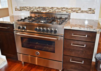 View of high capacity Bertazzoni gas range and adjacent cabinetry.