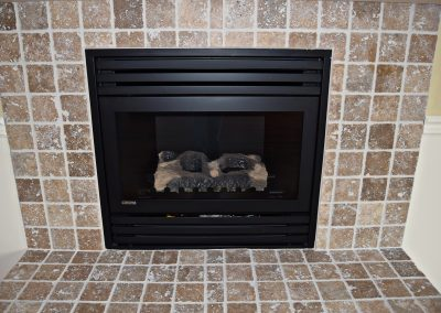 Close-in view of fireplace with custom-tiled surround.