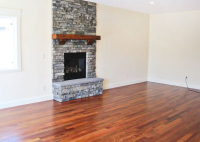 View of living area hearth with optional floor-to-ceiling stonework and hardwood mantel.
