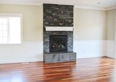 View of living area hearth with modern tile foundation and fireplace.
