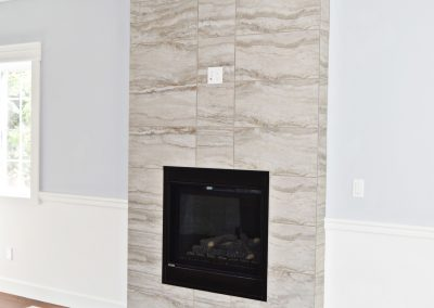View of a transitional-style fireplace with a floor to ceiling hearth.