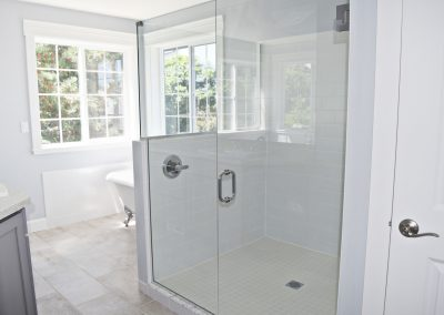 View of a spacious dual head shower in the well-lit master bathroom.