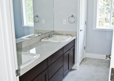 A double-sink with the doorway to the linen closet on the far side.