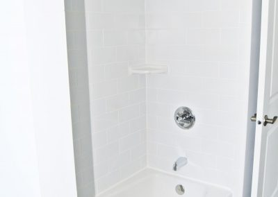 View of a guest bathroom's tiled bathtub and shower enclosure.