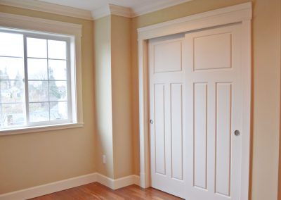 View of guest bedrooms closet, with continuous hardwood flooring.