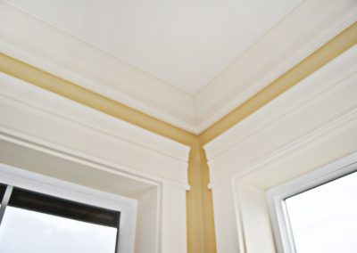 Detail view of crown moulding and interior window trim.